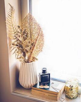 Perfumes femininos e jóias de ouro estavam sobre uma pilha de livros no peitoril da janela. decoração da casa na cor dourada