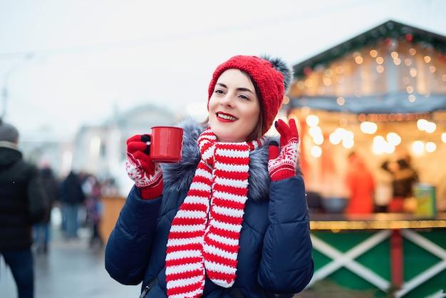 Perfurador bebendo da jovem mulher no mercado do natal.