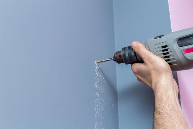 Perfurando uma parede cinza com uma broca