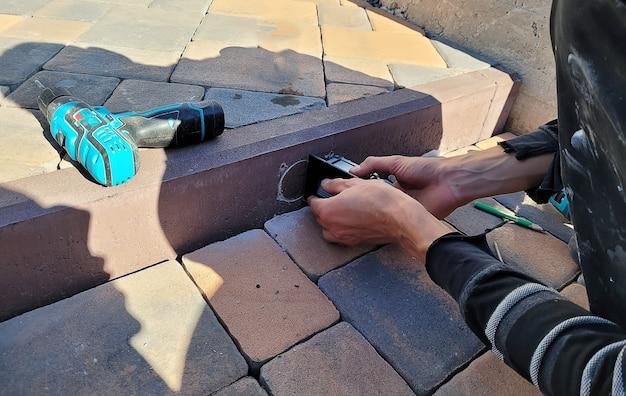 Perfurar um meio-fio de concreto para instalar a luminária. foco seletivo