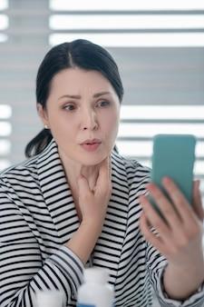 Pergunta, consulta. mulher adulta focada, olhando para a tela do smartphone no braço estendido, a outra mão tocando seu pescoço.