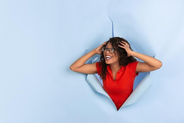 Perguntou-se, chocada, atônita, alegre mulher afro-americana em papel azul rasgado