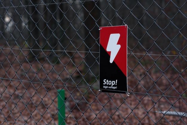 Perigo sinal preto vermelho com um raio na grade