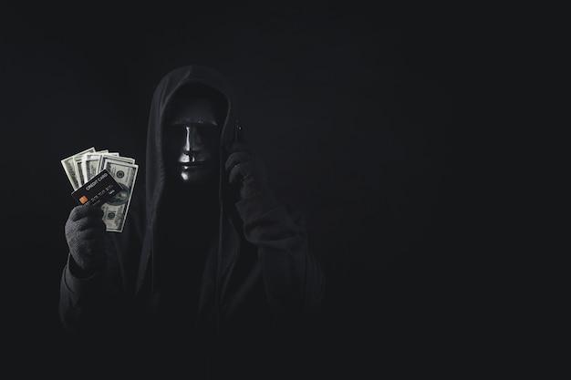 Perigoso hacker anônimo usando um smartphone encapuzado segurando um cartão de crédito e notas bancárias