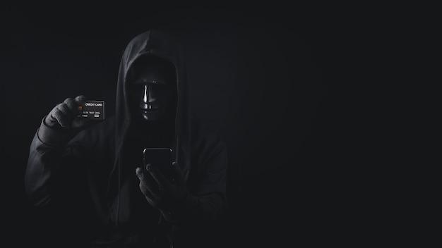 Perigoso hacker anônimo usando um smartphone encapuzado segurando um cartão de crédito