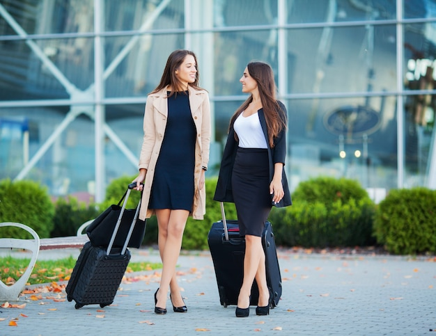 Período de férias. duas meninas felizes viajando juntos para o exterior, carregando bagagem mala no aeroporto