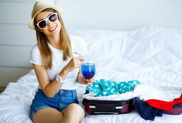 Período de férias. jovem linda garota senta-se na cama e detém no