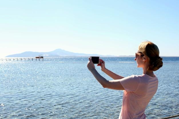 Período de férias. retrato colorido de uma bela jovem tirando um retrato de selfie com seu smartphone perto da piscina. foto de uma jovem atraente tirando uma foto com seu celular perto do mar