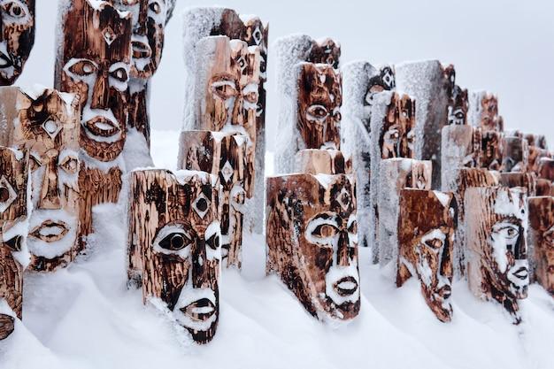 Perm krai, rússia - 2 de janeiro de 2021: fragmento de um objeto de arte coberto de neve na forma de um grupo de ídolos representando figuras antropomórficas