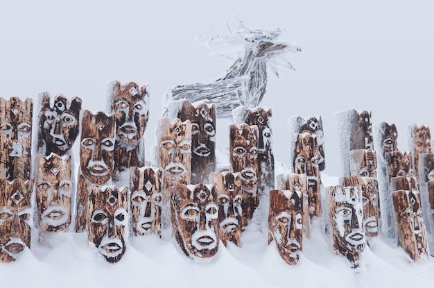 Perm krai, rússia - 2 de janeiro de 2021: objeto de arte de madeira coberto de neve - grupo de ídolos representando figuras antropomórficas e alces