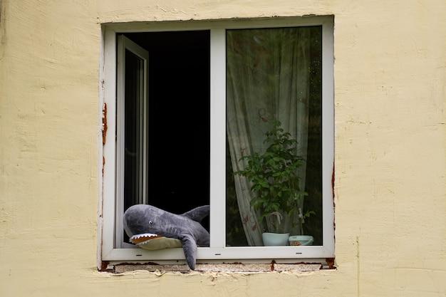 Perm, rússia - 23 de agosto de 2021: tubarão de brinquedo espiando pela janela
