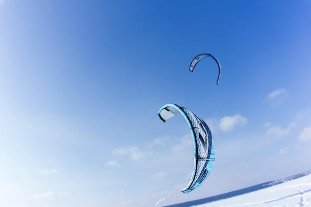 Perm, rússia - 23 de fevereiro de 2018: duas pipas para snowkiting, voando baixo sobre a neve contra o céu