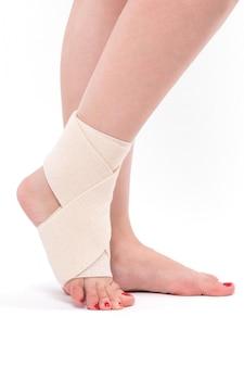 Perna da mulher amarrada com uma atadura elástica, tornozelo pé