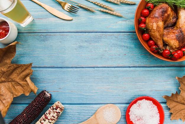 Perna de frango assado; na tigela com sal; sai; cerveja; garfo; faca de manteiga; milho na mesa de madeira