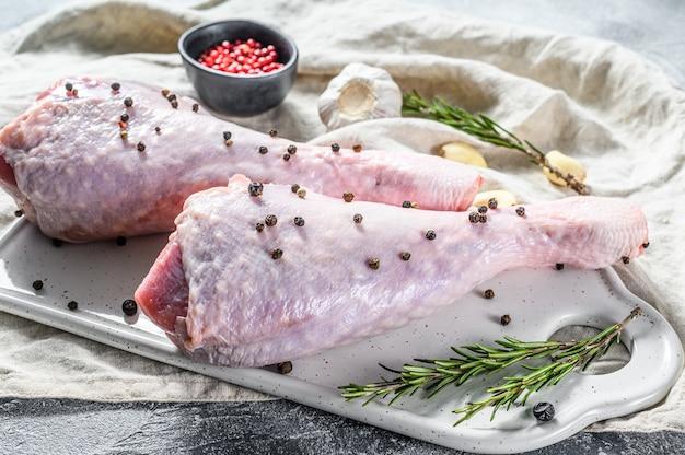 Perna de frango cru com especiarias em uma placa de corte branca. .
