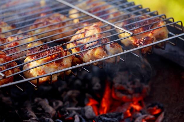 Perna de frango grelhado sobre chamas em um churrasco.