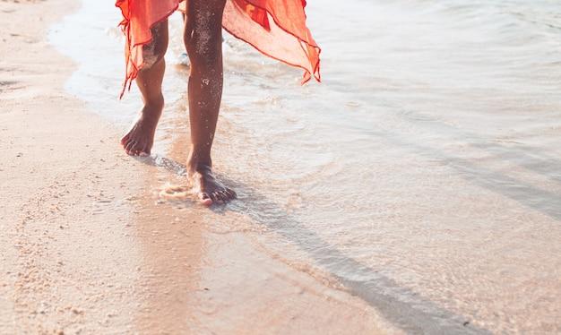 Perna de menina criança correndo na praia com água espirrando nas férias de verão