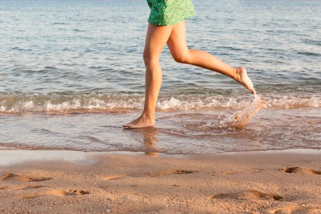 Perna de mulher correndo na praia com salpicos de água. férias de verão. pernas de uma menina andando na água no pôr do sol