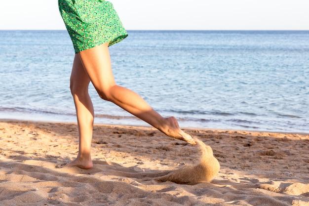 Perna de mulher correndo na praia de areia. férias de verão.
