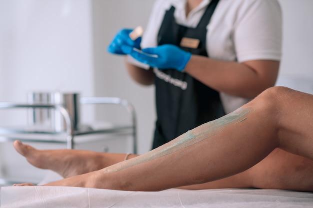 Perna de mulher de cera de esteticista com tira de cera em clínica de beleza