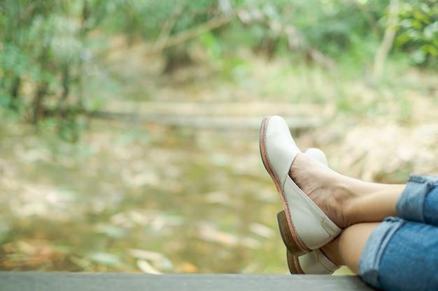 Perna de mulher e sapato que sentado no cais de madeira