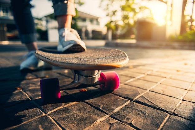 Perna de mulher em surf skate na estrada