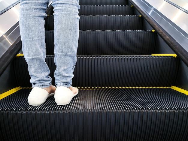 Perna de mulher viajando na escada rolante.