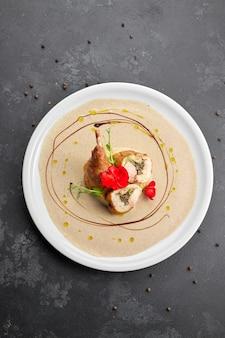 Perna de pato recheado com molho, em um prato branco, sobre um fundo escuro