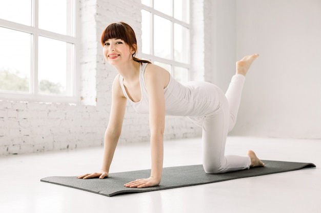 Perna de treinamento jovem sorridente na esteira na academia. mulher praticando ioga, fazendo exercício de burro, malhando, vestindo roupas esportivas, estúdio de ioga