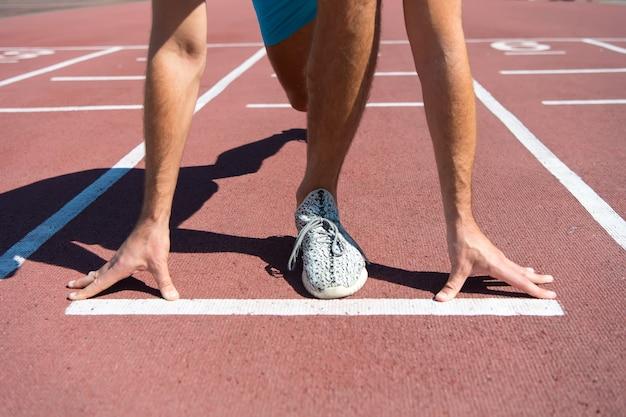 Perna do homem começa a competição correndo na pista da arena ensolarado verão ao ar livre, treino e saúde, esporte