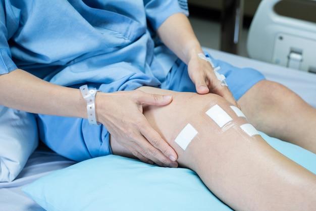 Perna do paciente de cirurgia do joelho do ligamento pcl deitado na cama na enfermaria no hospital com gesso de bandagem estéril na ferida.