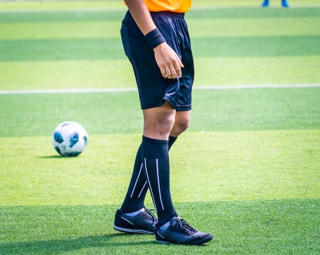Perna e pé de árbitro de futebol de futebol em um estádio de campo de competição de futebol com camisa amarela