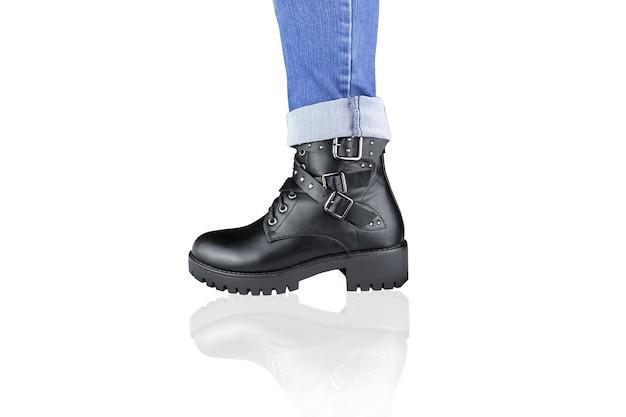 Perna em jeans azul e bota preta com cordões e fivelas. isolado no branco.