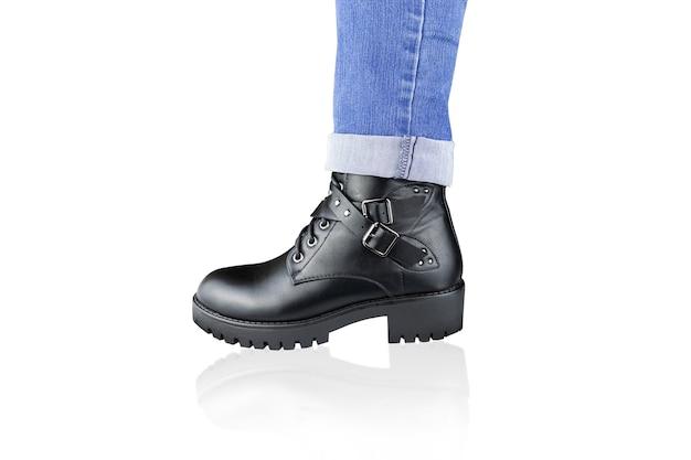 Perna em jeans azul enrolado e bota preta com fivelas e alças, isolada no branco.