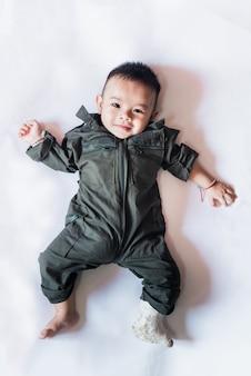 Perna esquerda da criança asiática do bebê do litlle na tala, coloc na cama.