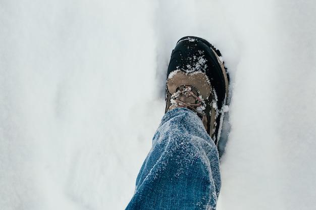 Perna masculina em um sapato, andando na neve