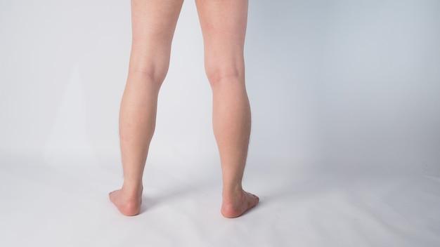 Perna traseira e descalço de homem asiático com pé no fundo branco.