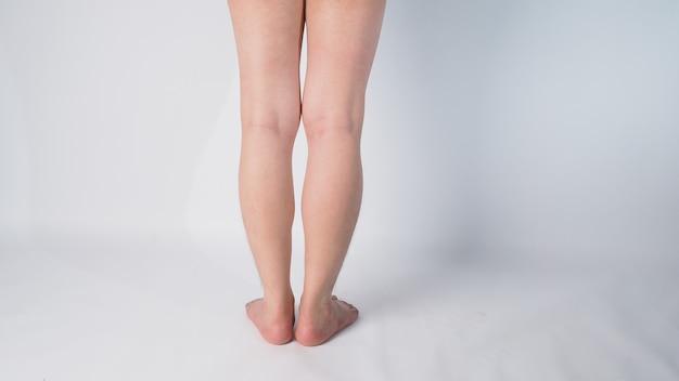 Perna traseira e descalço de homem asiático com pé perto de fundo branco.