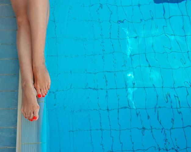 Pernas adultas de mulher branca européia européia com pedicure laranja na piscina