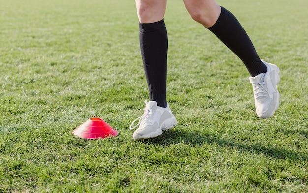 Pernas atléticas correndo através de cones