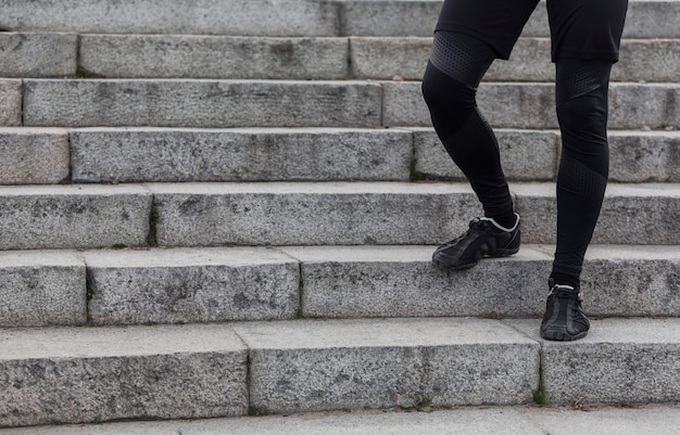 Pernas atléticas masculinas andando nas escadas