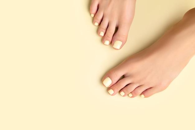 Pernas bonitas da mulher bem cuidadas com desenho de unhas de verão na superfície amarela