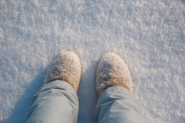 Pernas, botas de inverno na neve