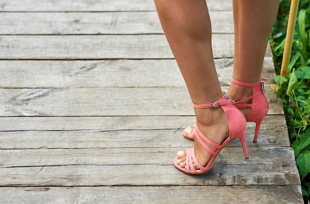 Pernas bronzeadas de verão de uma jovem com salto