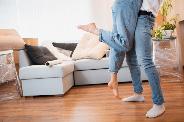Pernas close-up vista. casal jovem primeira vez proprietários de casa comemoram o conceito de dia em movimento, marido homem levantando segurando a esposa em pé perto de caixas no novo apartamento em casa
