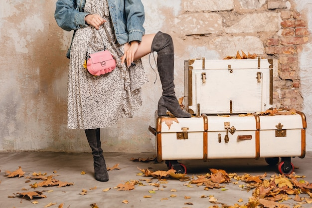 Pernas com botas de mulher loira elegante e atraente em jeans e jaqueta grande posando contra a parede na rua