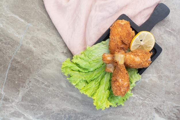 Pernas crocantes de frango com alface e limão no tabuleiro escuro