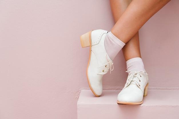 Pernas cruzadas com sapatos oxford brancos