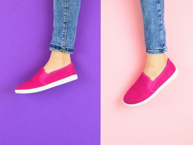Pernas da garota de tênis vermelho e calça jeans no chão roxo e rosa. a vista do topo.