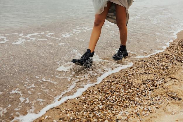 Pernas da garota em elegantes botas pretas em uma praia arenosa.